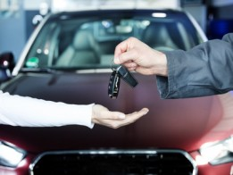 Key delivery between customer and mechanic in front of new car